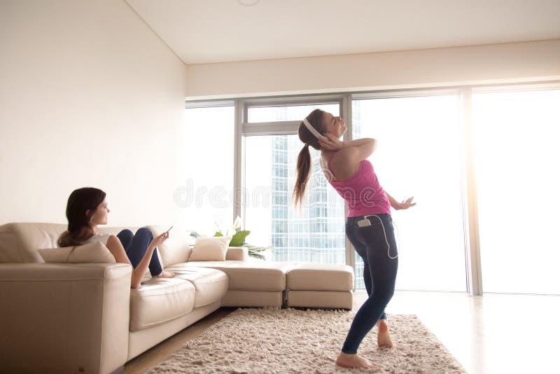 Hörende Musik des jungen Mädchens und ihre Freundin, die auf Sofa sich entspannen lizenzfreies stockbild