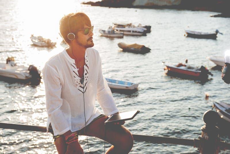 Hörende Musik des jungen Mannes mit Kopfhörern von der Tablette in einem vacat stockfotografie