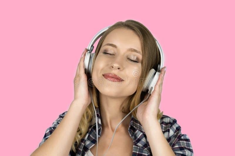 Hörende Musik des Mädchens in Kopfhörer lokalisiertem rosa Hintergrund lizenzfreie stockfotos