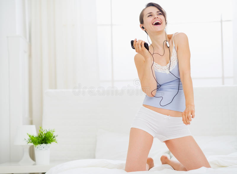 Hörende Musik des Mädchens und Tanzen auf Bett lizenzfreie stockfotos