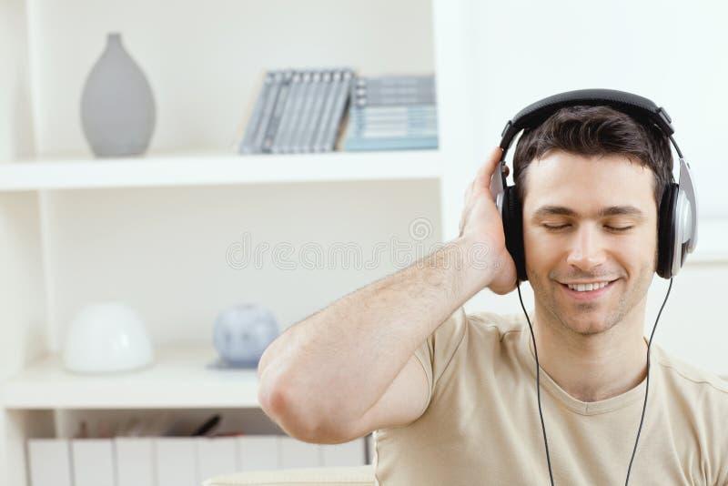 Hörende Musik des Mannes mit Kopfhörern stockfotografie