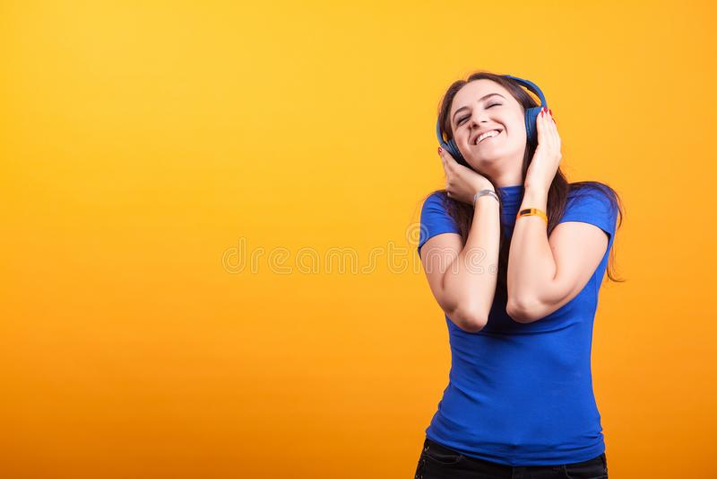 Hörende Musik schöner youg Frau mit ihren Kopfhörern lizenzfreie stockfotos