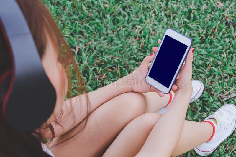 Hörende Musik vom intelligenten Telefon mit Kopfhörern lizenzfreie stockbilder