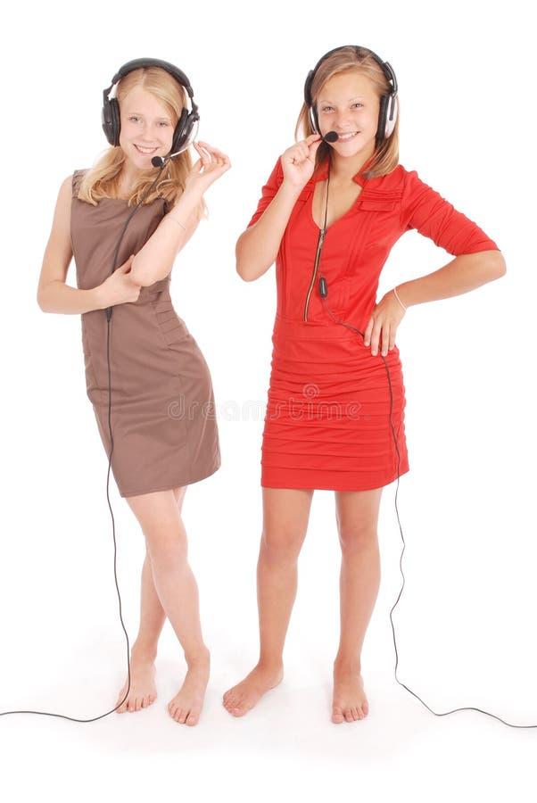 Hörende Musik von zwei hübschen Jugendlichen auf ihren Kopfhörern stockbilder