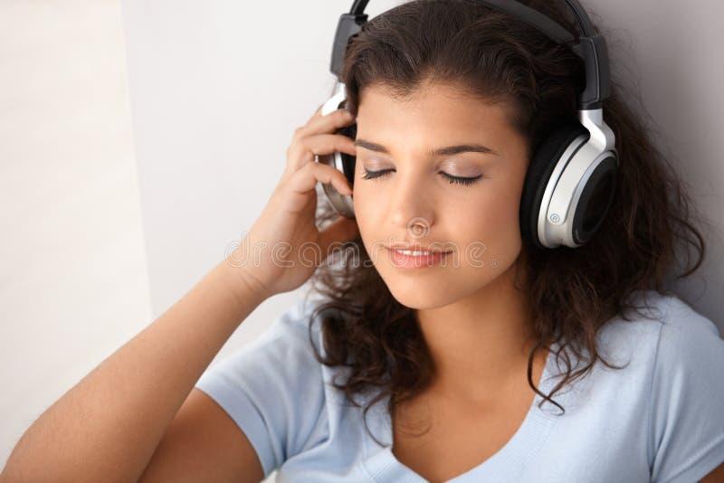 Hörende Musikaugen des Schulmädchens geschlossen stockbilder