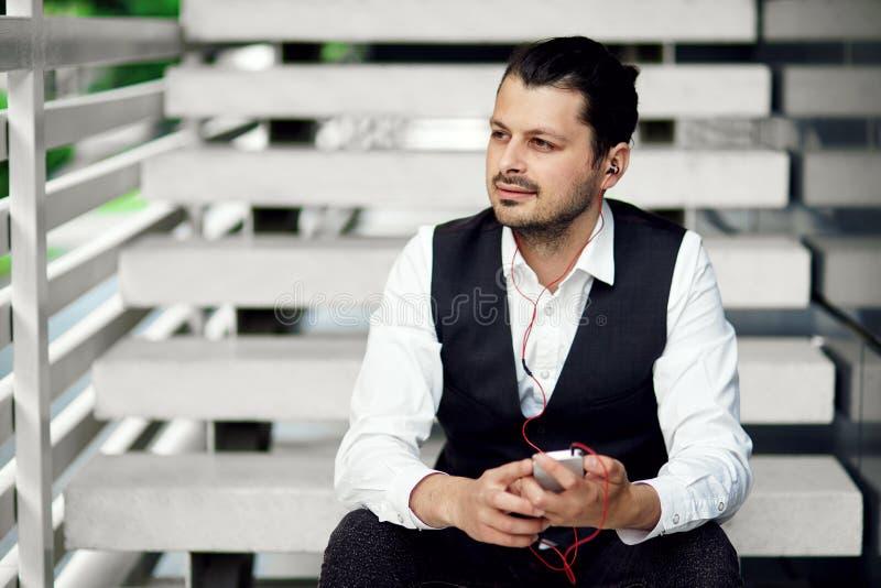 Hörende Musikkopfhörer des jungen Hippie-Mannes Attraktiver Mann mit einem Smartphone stockfotos