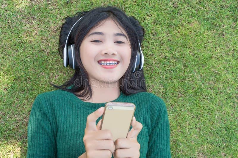 Hörende Musikkopfhörer des jungen Schönheitsmädchens im Freien stockfotografie
