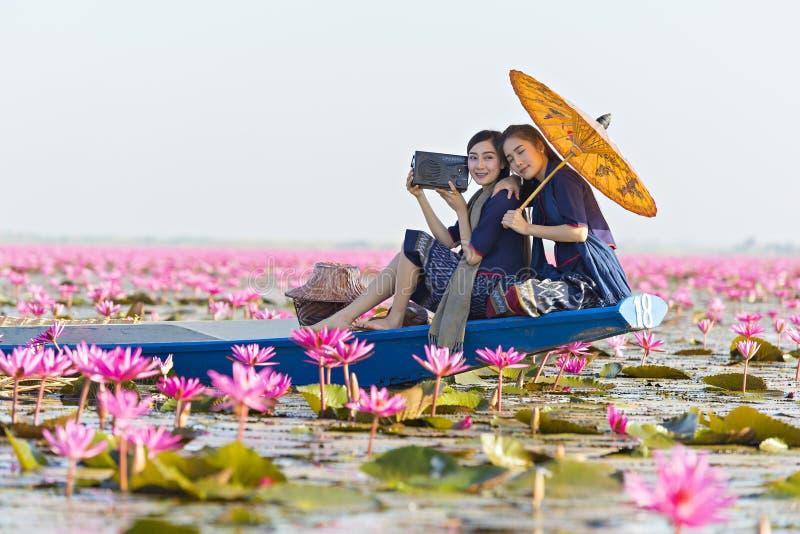 Hörender Radio Laos-Frau auf Boot im Blumenlotossee, Frau, die traditionelle thailändische Leute, rote Lotus Sea UdonThani Thaila lizenzfreie stockfotografie