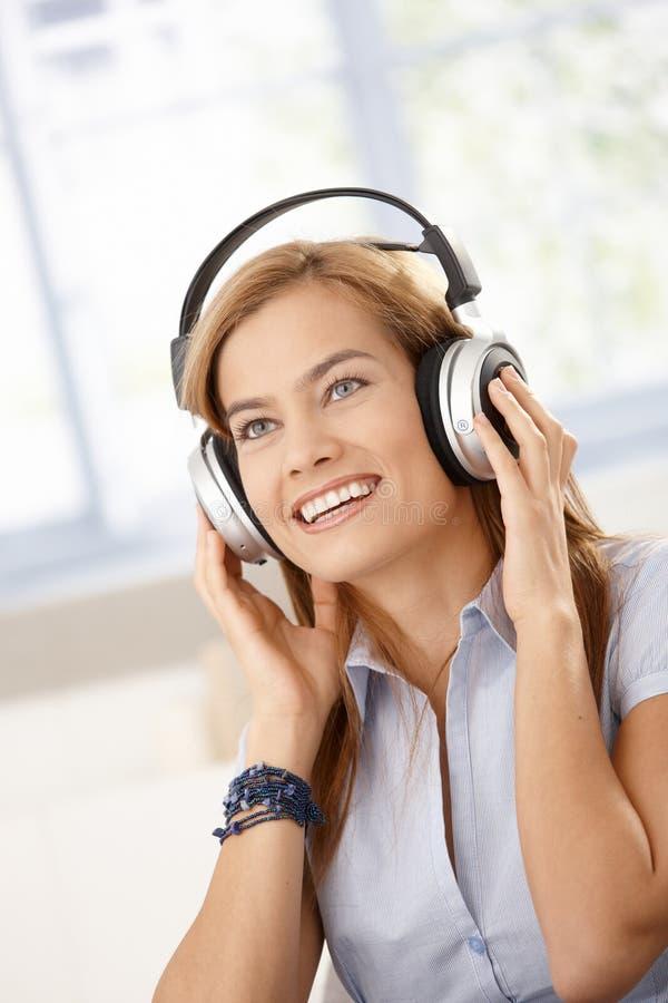 Hörendes Musiklächeln des attraktiven Mädchens lizenzfreies stockbild