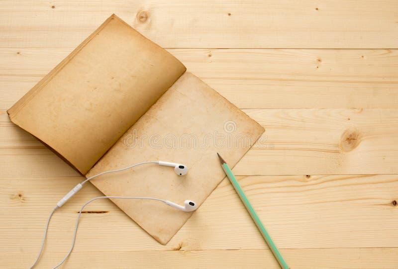 Hörlur, gammal bok och blyertspenna på den wood tabellen arkivfoton