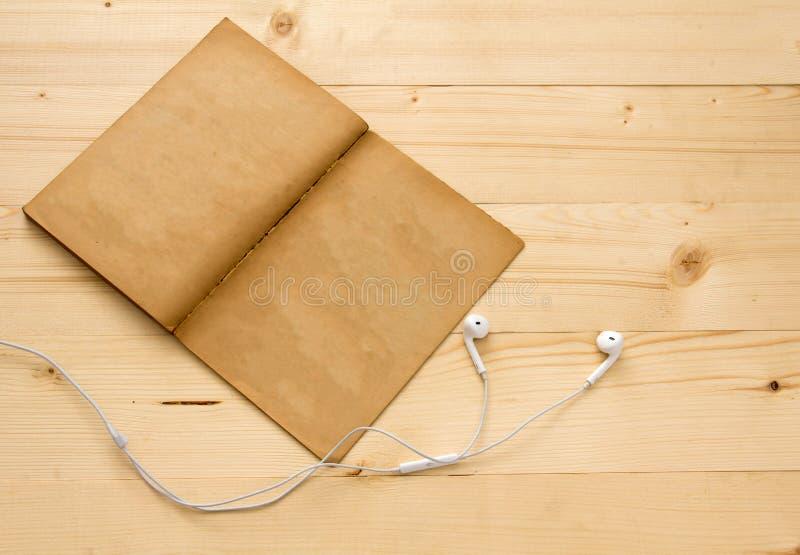 Hörlur gammal bok på den wood tabellen arkivbilder