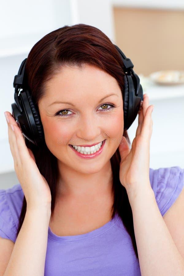 hörlurar lyssnar musik som ler till kvinnan royaltyfria bilder
