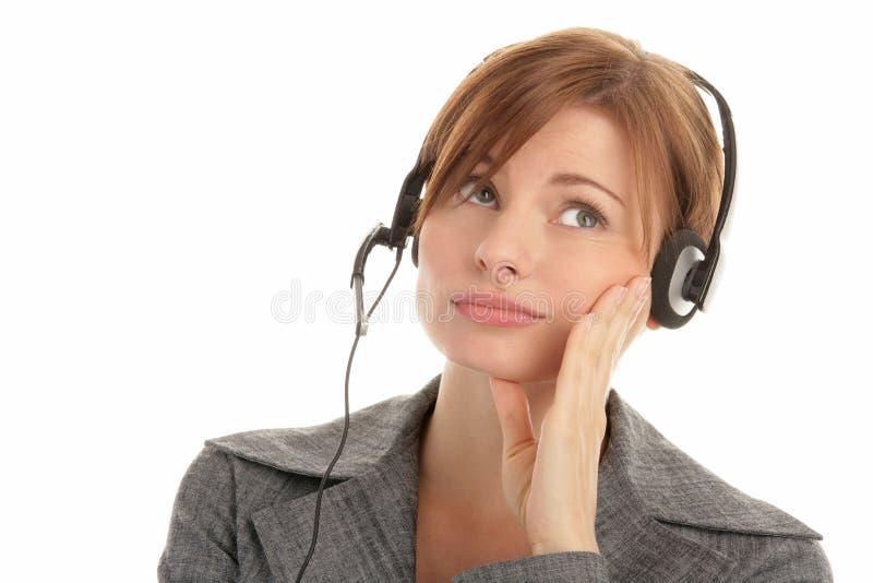 hörlurar med mikrofon tröttad slitage kvinna royaltyfri bild