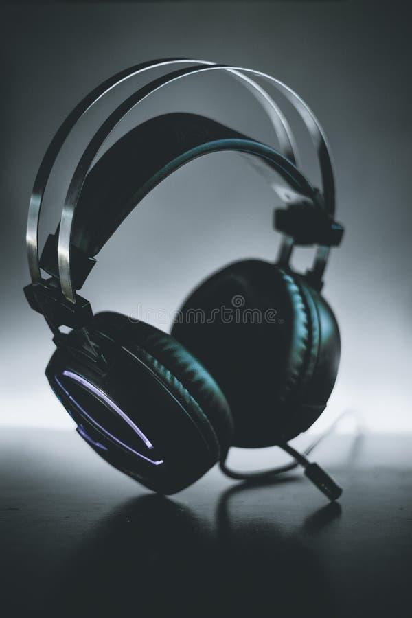H?rlurar med mikrofonmusikal & spela m?rk bakgrund f?r utrustningljus arkivfoto