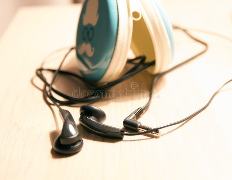 Hörlurar med trådar på tabellen, med, ett fall för hörlurar arkivbild