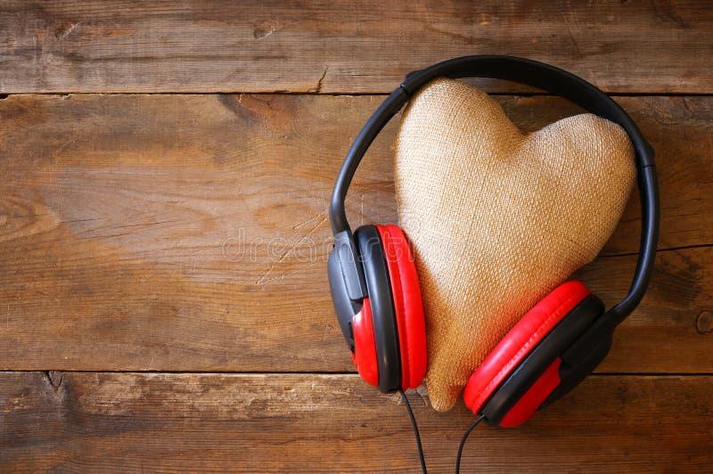hörlurar med tyghjärta över träbakgrund arkivbild