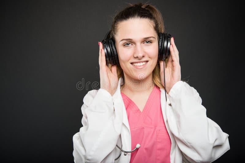 Hörlurar och le för attraktiv kvinnlig doktor bärande fotografering för bildbyråer