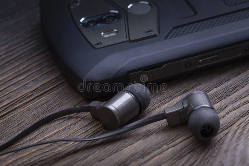 Hörlurar och mobiltelefon på trätabellsmartphonen med headphonen arkivfoton