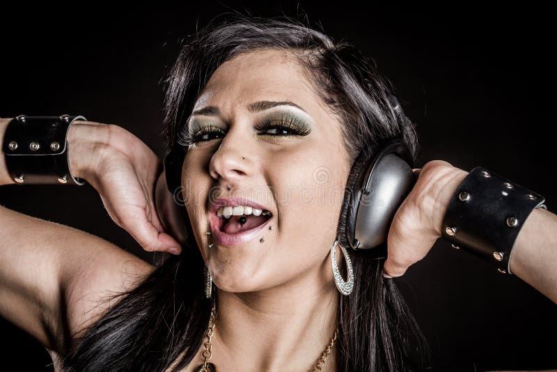 hörlurar som sjunger kvinnan royaltyfri foto