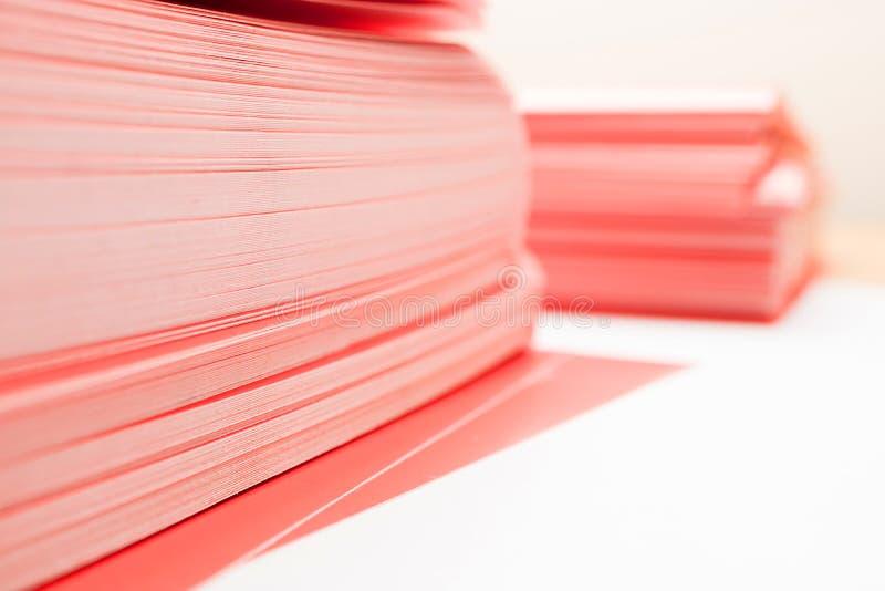 Hörn av en bunt av rött papper på en tabell, två högar av tätt papper royaltyfri foto