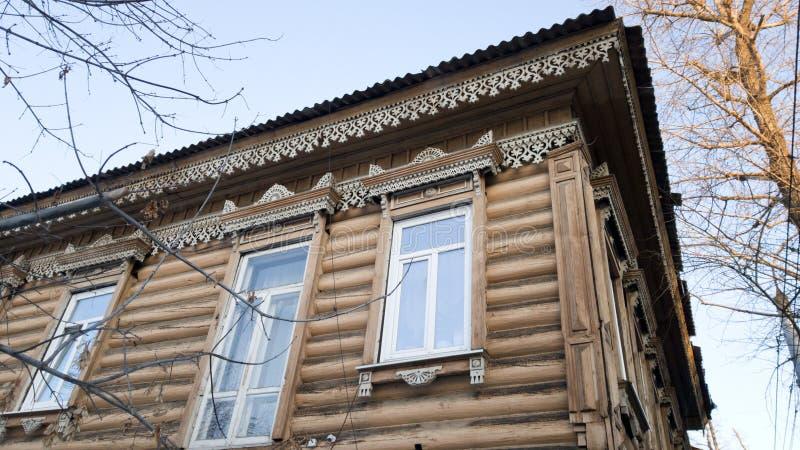Hörn av ett gammalt trähus med härliga sned detaljer och garneringar Gammal byggnad i Irkutsk, Ryssland royaltyfria bilder