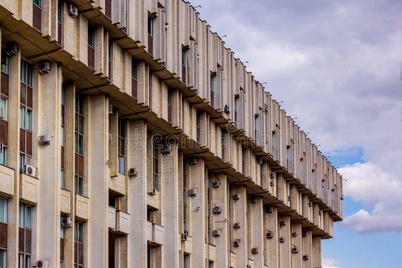 Hörn av stor konkret byggnad mot himlen med moln royaltyfri bild