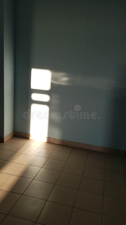 Hörn inom tomt rum och belagt med tegel golv med ljusa glänsande oskarpa solstrålar arkivfoto