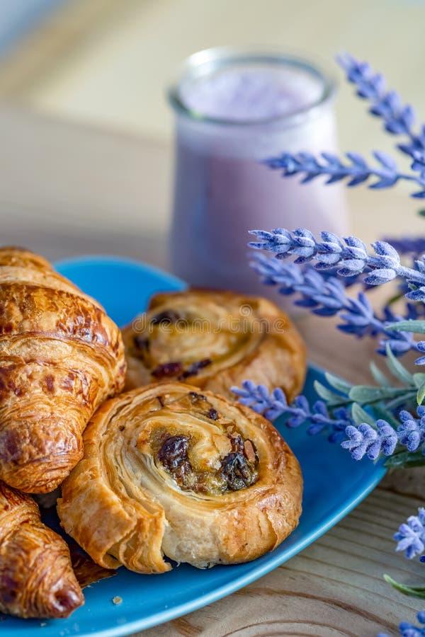 H?rnchen, Br?tchen mit Rosinen auf einer blauen Platte und Heidelbeerjogjurt im Glasgef lizenzfreie stockfotos