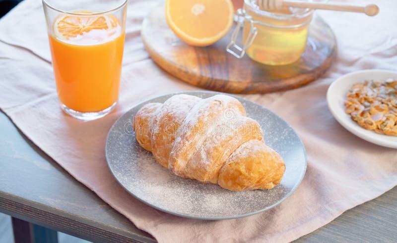 Hörnchen, Honigglas und Orangensaft auf Holztisch Gesundes Frühstück lizenzfreie stockfotos