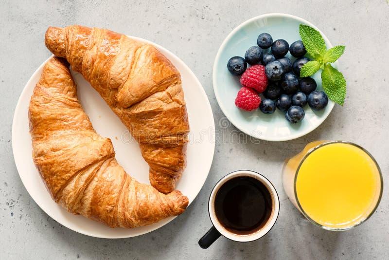 Hörnchen, schwarzer Kaffee, Orangensaft und frische Beeren stockfoto