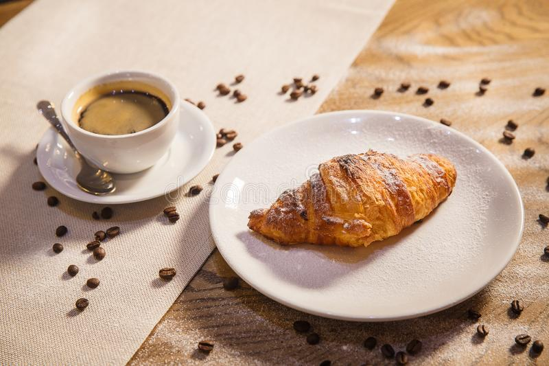 Hörnchen und Kaffee auf einem Holztisch, Kaffeebohnen zerstreuten auf eine Tabelle stockfoto