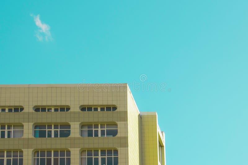 Hörnet av byggnaden med många fönster mot den blåa himlen fotografering för bildbyråer