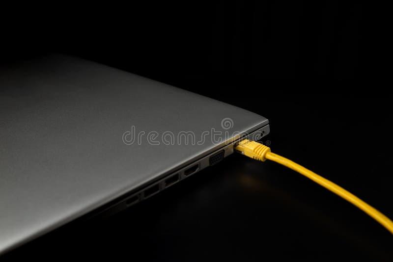 Hörnet av den gråa datoren och gul usb-tråd är på den svarta tabellen/bakgrunden Informationsdag om v?rld royaltyfri fotografi