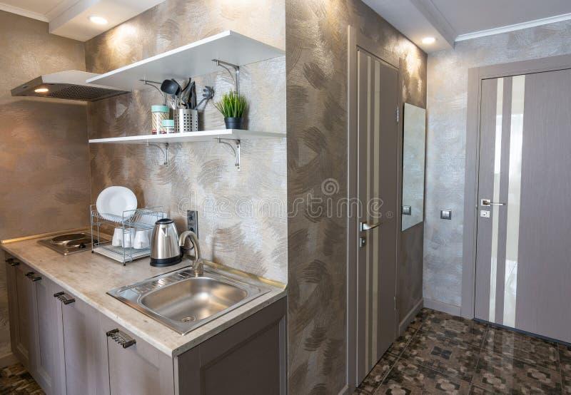 Hörnet av det lilla köket och ingången till hotellrummet royaltyfri bild