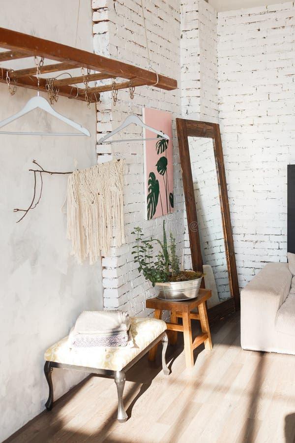 Hörnet av vinddesignrummet med vita tegelstenväggar, blommor i järn lägger in, avspeglar, arbeta som privatlärare åt Hängande kug arkivfoto