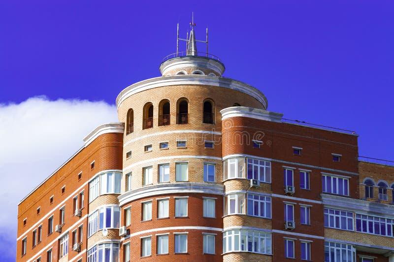 Hörnet och överkanten av ett tegelstenhöghus mot en blå himmel royaltyfri fotografi