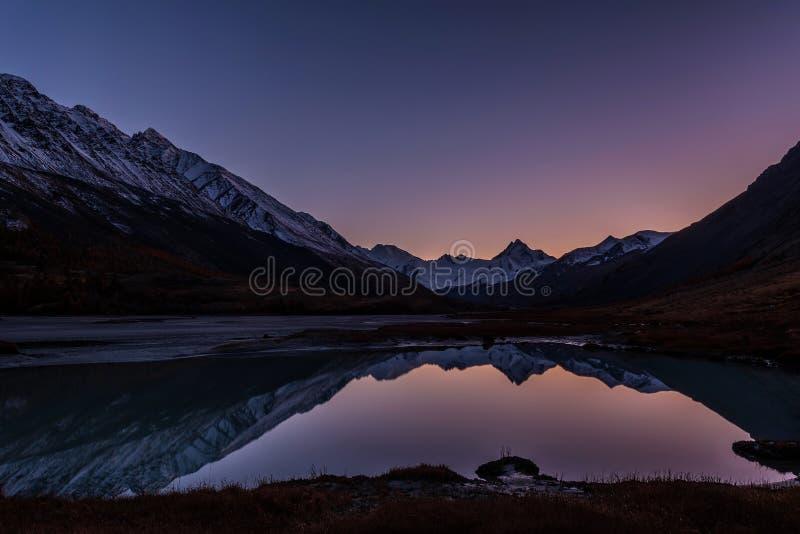 Höst för snö för reflexion för solnedgångbergsjö royaltyfri bild