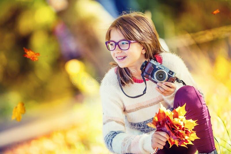 Höst Time Den tonårs- attraktiva gulliga unga flickan med höstbuketten och den retro kameran Ung flickafotografhöstsäsong arkivbilder
