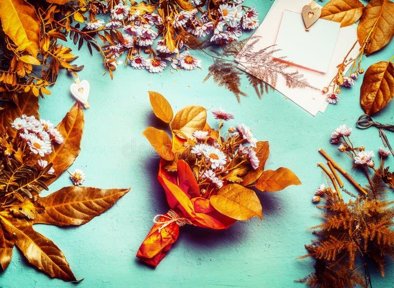 Höstblommabuketten med gulingsidor och rosa färger blommar på skrivbords- bakgrund, bästa sikt Utrymme för höstblomsterhandlarear royaltyfri bild