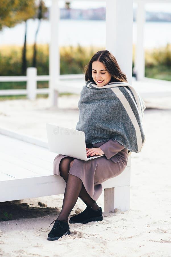 Hösten är kommande En härlig ung nätt flicka spenderar hennes tid på terrassen, medan arbeta på en bärbar dator royaltyfri fotografi