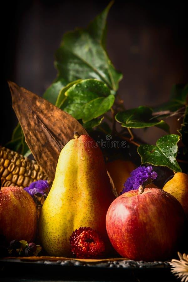 Hösten bär frukt på det mörka lantliga köksbordet på träbakgrund, sidosikt arkivbilder