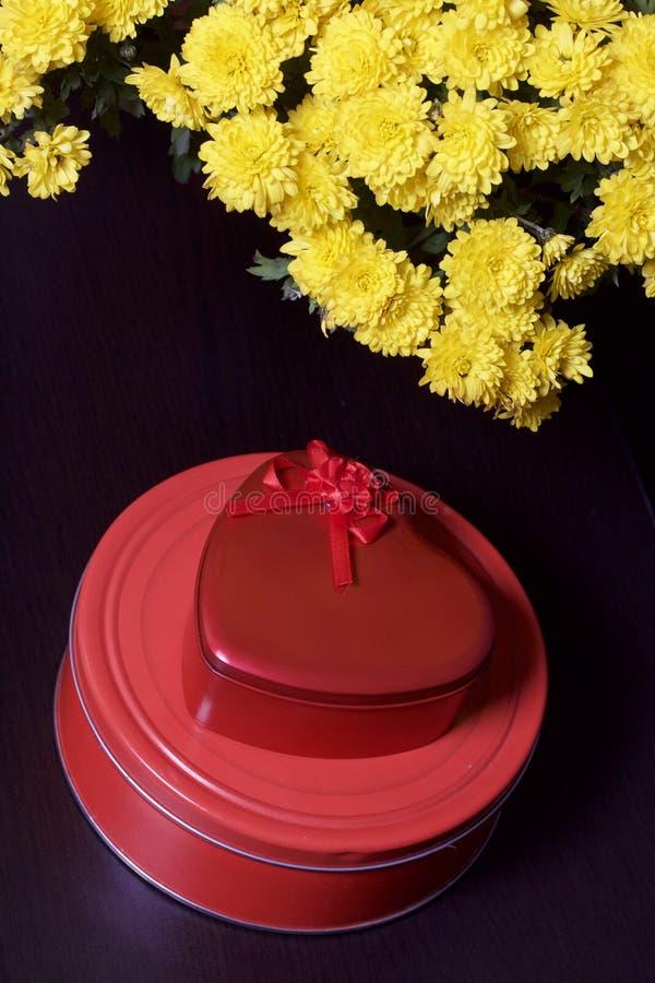 Hösten blommar i en kruka Gul chrysanthemum Nästa gåvor i tenn- askar arkivbilder