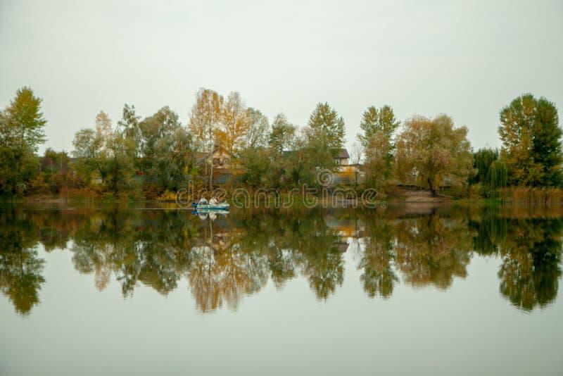 Hösten landskap Sjö, träd och by vid sjön stillhet Perfekt reflexion i vattnet royaltyfri foto