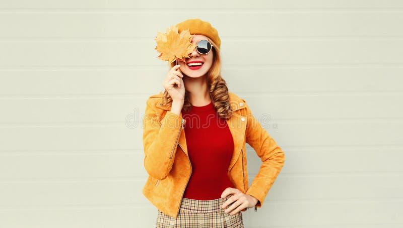 Hösten stående en glad leende kvinna som håller i handen gult maple lämnar sitt öga över grå väggen arkivfoto