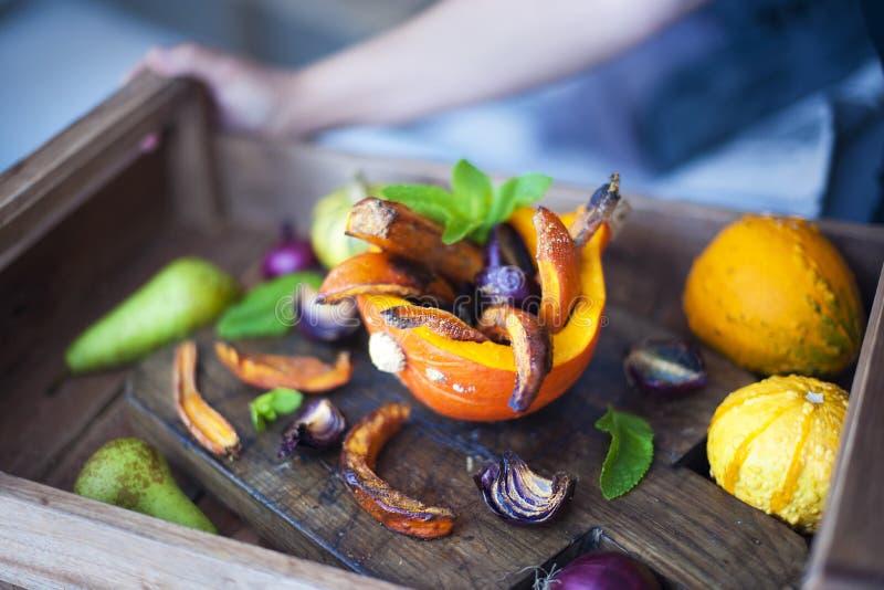 Höstfrukt pumpa och lökar som bakas med honung På en brun bakgrund royaltyfri foto
