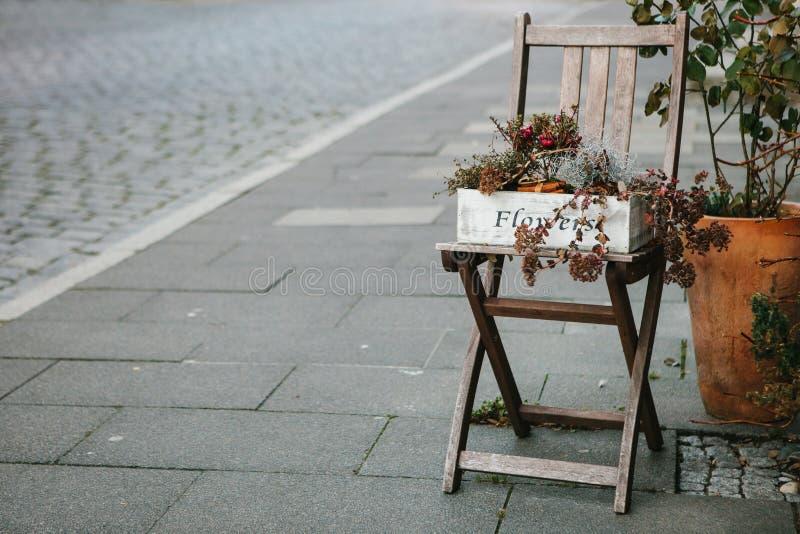 Höstgarnering med en stol och blommor på gatan royaltyfri bild