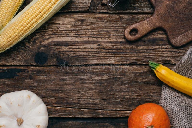 Höstgrönsaker: pumpor och havre med gulingsidor och snittet stiger ombord på en träbakgrund royaltyfri foto