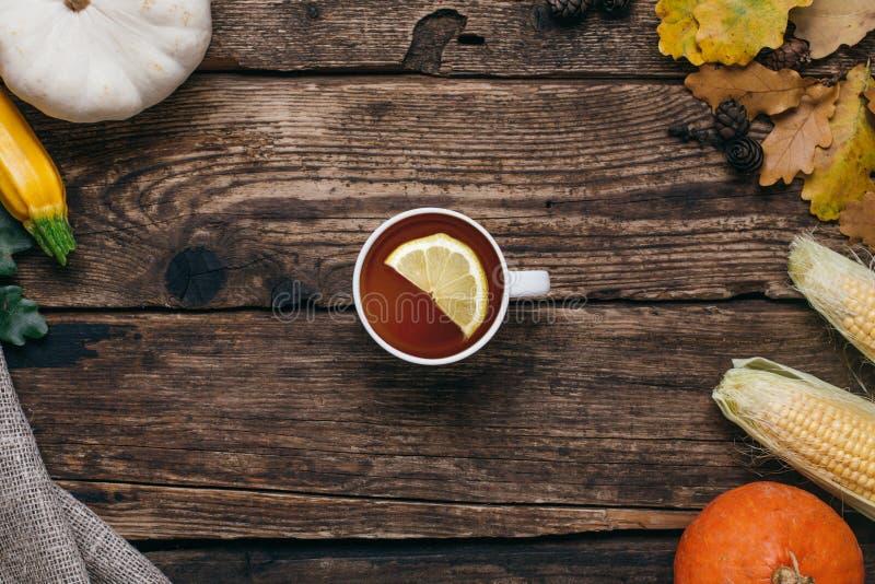 Höstgrönsaker: te, pumpor och havre med gulingsidor på en träbakgrund royaltyfria foton