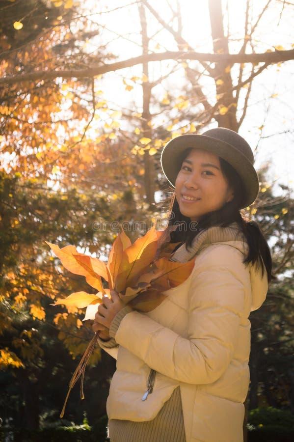 Höstkvinna med gula nedgångsidor royaltyfri bild
