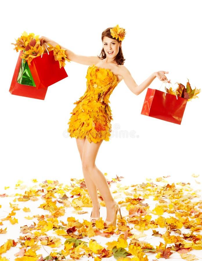 Höstkvinna med shoppingpåsar i klänning av lönn. Vit bakgrund arkivbilder